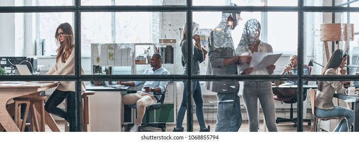 Talking business details. Full length of young modern people working and communicating together while standing behind the glass wall in the board room