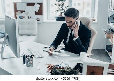 Talking business details. Handsome young man in full suit talking on the phone while sitting at the office desk