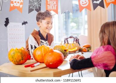 Talking to friend. Beaming funny boy wearing Halloween skeleton costume talking to his beautiful friend