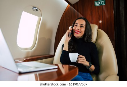 Talking with a friend. Close-up photo of a beautiful woman in a casual outfit, who is talking on the phone and drinking black coffee during her flight in private jet.