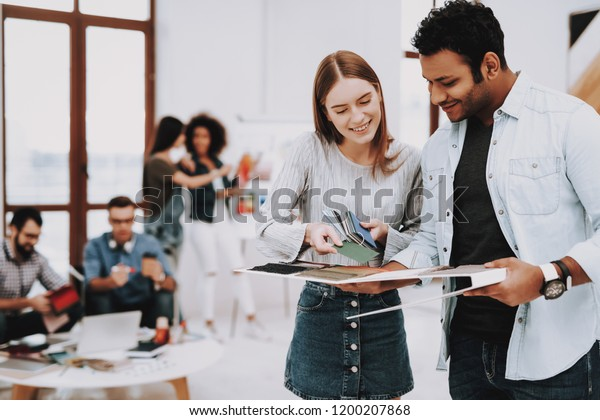 Talking. Guy and Girl. Young Specialists. Designers. Choose Colors for Design. Work Together. Office. Teamwork. Discussion. Brainstorming. Design Studio. Multi-Ethnic. Project. Creative. Workplace.