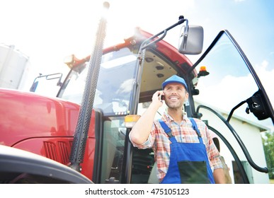 Talking on the phone in front of the tractor