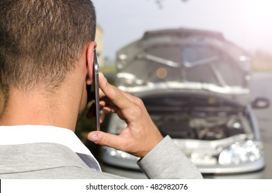 Talking on the phone. Man calling for help. Car break down. Car service. Tow service. Emergency.