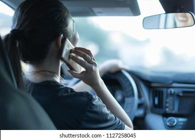 Hablando por teléfono mientras conduce. Enviando mensajes de texto y conduciendo. Conductor distraído detrás del volante.