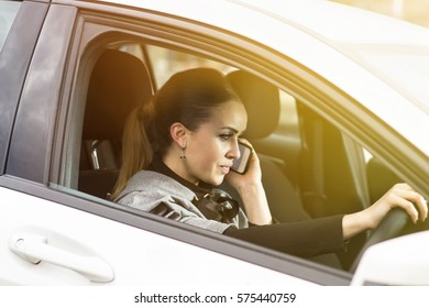 Talking on the phone while driving. Beautiful woman making a phone call in her car.