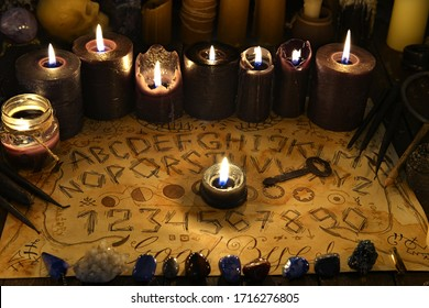 Talking spiritual board with black candles and old key. Wicca, esoteric and occult background with vintage magic objects for mystic rituals. Halloween and gothic concept