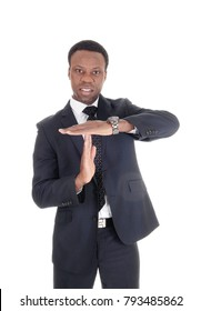 A tall African American business man standing in a suit and signals