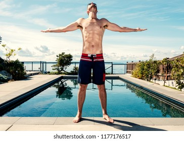 Tall athletic body caucasian male with arms raised looking toward the sky in mid day sun by swimming pool wearing swim trunks.