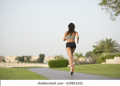Tall athletic fitness model running in a park showing beautiful long legs and hard body