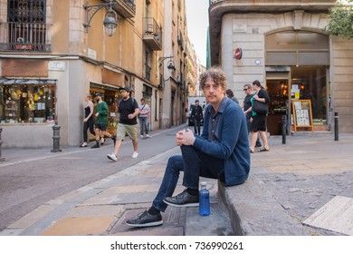 Tall, attractive forty something man sits in a plaza in Barcelona. He wears retro, vintage style clothing with a blue sweater. He has a kind face.