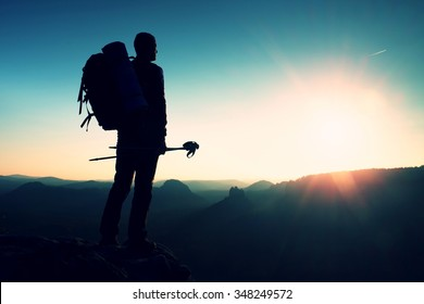 Tall backpacker with poles in hand. Sunny spring daybreak in rocky mountains. Hiker with big backpack stand on rocky view point above misty valley. Hiker watching blue daybreak. Hiking ambition.
