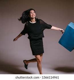 A tall, beautiful and elegant Korean Asian woman in a black dress is jumping and prancing in a studio with a blue briefcase and laughing out loud as she jumps and skips.