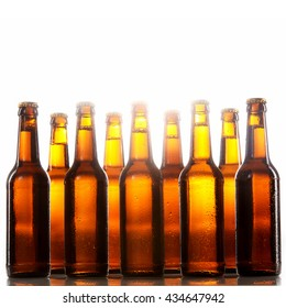 Tall beer bottles with no labels and metal caps stand two rows deep against a white background