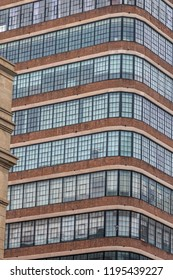 A tall building with many window. The viewer is looking at the corn of the building. A red brick facade is below the windows. A white brick facade is above the windows. This is a vertical picture.