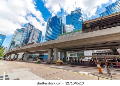 Tall buildings on the sky light rail and ground bus stops.