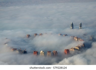 tall buildings rise above ground fog as viewed from above in Doha, Qatar