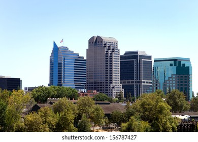 Tall buildings show above the tree in a skyline view of the city of Sacramento, California.