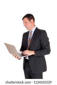 A tall business man standing in a dark suit and tie holding his laptop