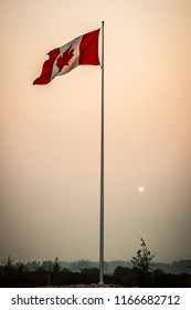 Tall Canadian flag blowing in the wind in BC Canada. A small, dim, red sun caused by the wildfires and forest fires in the bc can be seen setting in the distance behind smoky and hazy forest and trees