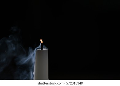 tall candle with smoke trail in the dark environment, shallow focus