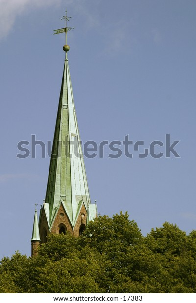 A tall church steeple behind some trees