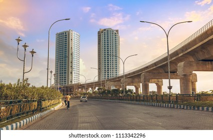Tall city buildings with under construction over bridge alongside highway road at Rajarhat, Kolkata India.