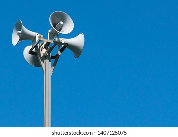 A tall column with four gray loudspeakers in a circle against a clean blue sky. Hazard warning system. The possibility of placing your test or image.