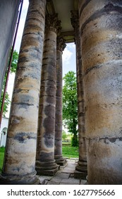 tall columns on a background of green wood with architectural elements small capitals and volute