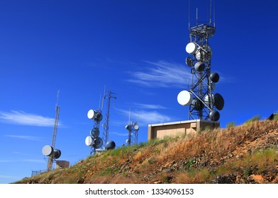 Tall communication towers against blue sky