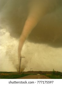 A tall cone-shaped tornado at close range churns the dirt in a nearby field.