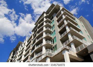 Tall contemporary condo building on the beach with blue skies and puffy clouds as background.