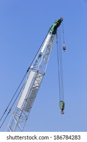 Tall Crane in construction site.Two Pulley and hook still hang on.