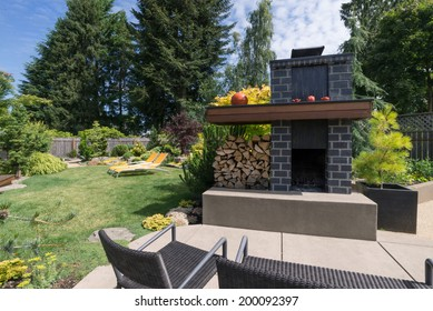 A tall, custom-designed fireplace with grey bricks and plenty of firewood sits on an inviting patio with a beautifully landscaped yard in the background.
