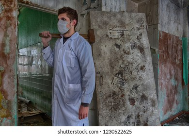 Tall and dangerous man in medical mask and white medical gown hold big hammer in his hands inside ruined medical clinic. Maybe psycho surgeon or bonecrusher or building destruction worker