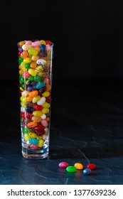 A tall decorative glass filled with brightly coloured jelly beans isolated against a black background.