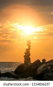 A tall, elegant, impressive balancing stones figure shoot in a back light during sunset on a beach with a huge sun flare in the back. Exotic nature scene perfect for travel and adventure designs.