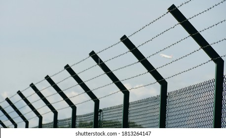 A tall fence around the ground of Zurich Airport made of woven wire and enhanced with barbed wire as protection from unauthorized entry.  There is a vague silhouette of a plane on the background.