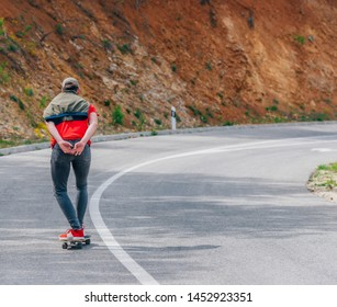 Tall fit male longboarder riding his longboard downhill on a sunny day high in nature while wearing a red shirt, green hat, and grey jeans.