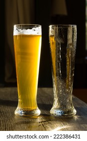 Tall Glass of Beer Beside Empty Glass on Wooden Table in Sunlight