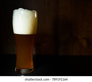Tall glass of beer on dark wooden background. with copy space.
