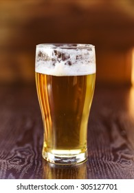 tall glass of beer on wooden background