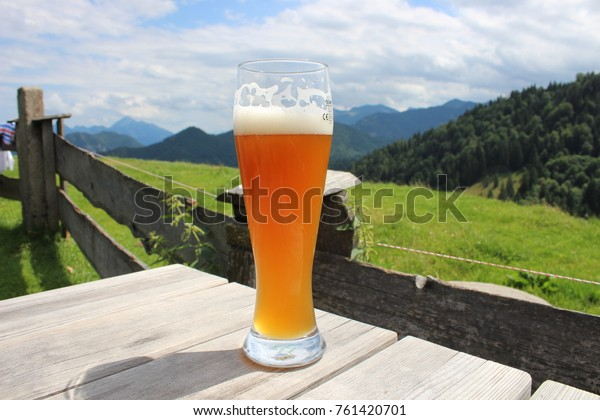 A tall glass of cold German wheat beer (Weissbier) on a wooden table with the green mountains of the German Alps in the background