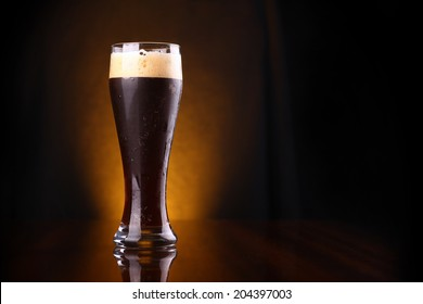 Tall glass of dark beer over a dark background lit yellow