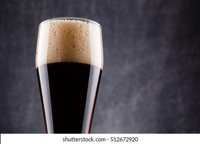 Tall glass of dark beer over a dark textured wooden background