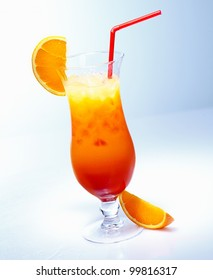 Tall glass of iced fresh fruit orange cocktail with a straw against a pale blue background in a tropical vacation concept