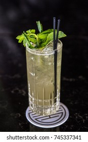 Tall Glass of Lemonade Spritzer with Ice and Fresh Green Mint and Straw