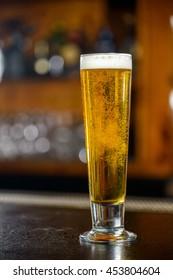 Tall glass of light beer in a dark bar