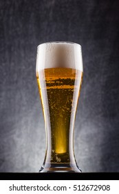 Tall glass of light beer over a dark textured wooden background
