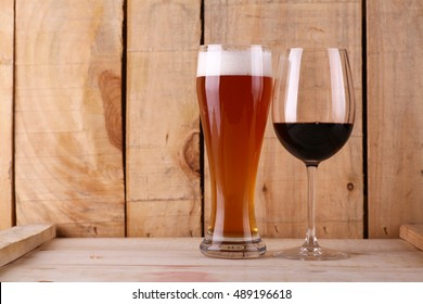 Tall glass of light beer and red wine glass over a textured wood background