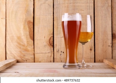 Tall glass of light beer and white wine glass over a textured wood background